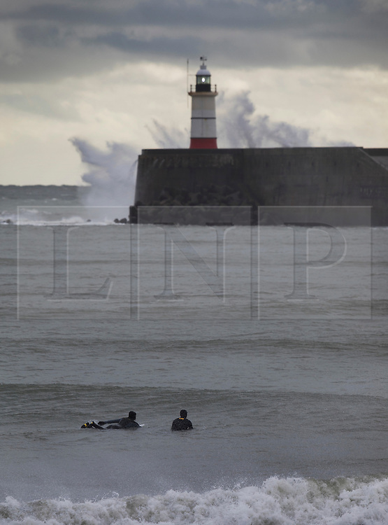 © Licensed to London News Pictures. 20/11/2016. Newhaven, UK. Surfers watch as Storm Angus whips up the sea at Newhaven lighthouse. The south east has experienced winds of up to 80 miles per hour as the first named storm of the season hits. Photo credit: Peter Macdiarmid/LNP