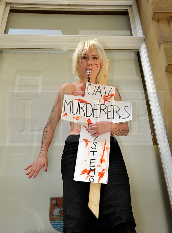 NOTE TO EDITORS - CONTAINS NUDITY © Licensed to London News Pictures. 02/04/2012.  Performance artist and human rights activist Milly Fish protests against unmanned aerial vehicles or drones used for military operations in Afghanistan and elsewhere and for surveillance in the UK.  The protest was outside a conference on UAVs at Armada House in Telephone Avenue in central Bristol.  Police made several arrests...Photo credit : Simon Chapman/LNP