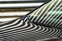 Reflejo de cerramiento de obra de chapa ondulada de acero galvanizado sobre la carrocería de un vehículo en Sevilla./ Reflection of a construction site fence over a vehicle at Seville, Spain.