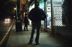 Children standing in street outside shop,