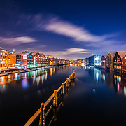 """Trondheim with picturesque, tiny, wooden houses. This idyllic neighbourhood on the east side of the Nidelva river features old timber buildings, originally the homes of the working class. Now restored, Bakklandet is a charming mixture of houses, shops and cafés.<br /> Nidelva river cuts through the city, winding its way along the Nidarosdomen park and picturesque areas, with the historic, wooden wharf houses lining its sides towards the mouth at the Trondheim fjord, and the beautiful, wooden bridge """"Gamle Bybro"""" crossing the rive. <br /> <br /> I have taken this photo in a calm winter nights with absolutely gorgeous lights around."""