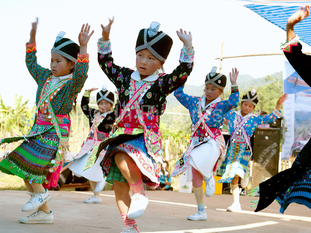 White Hmong girls dancing at Ban Hauywai Hmong New Year festival, Phongsaly province, Lao PDR. The Hmong celebration of New Year is based on the lunar calendar. This important time is an opportunity to honour ancestors and spirits through offerings and rituals and to partake in games, sports, feasts, shows, bullfights and courtship. The Hmong are the third largest ethnic group in Laos. One of the most ethnically diverse countries in Southeast Asia, Laos has 49 officially recognised ethnic groups although there are many more self-identified and sub groups. These groups are distinguished by their own customs, beliefs and rituals. Details down to the embroidery on a shirt, the colour of the trim and the type of skirt all help signify the wearer's ethnic and clan affiliations.