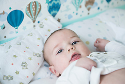 Close-up of baby boy lying on bed