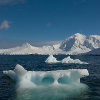 Icebergs float in the Neumayer Channel below mountains on Anvers Island, Antarctica.