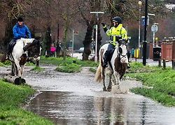 © Licensed to London News Pictures. 30/01/2021. London, UK. Horse riders trot through flooded bridleways on Wimbledon Common in South West London this morning as the Met Office issue weather warnings for rain and flooding for large parts of England. The Met office has issued weather warnings for much of the UK this weekend for snow, torrential rain and flooding with disruption to travel as the stormy weather continues. Photo credit: Alex Lentati/LNP<br /> <br /> *Permission Granted*