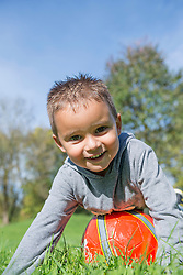 Portrait young small boy red football meadow