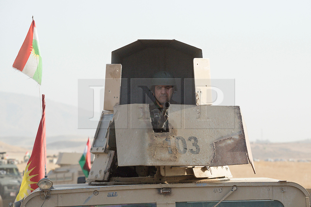 20/10/2016. Bashiqa, Iraq. A Kurdish peshmerga machine gunner hunkers down in the turret of his armoured Humvee as he takes part in a large offensive to retake the Bashiqa area from Islamic State militants today (20/10/2016).<br /> <br /> Launched in the early hours of today with support from coalition special forces and air strikes, the attack is part of the larger operation to retake Mosul from the Islamic State, and involves both the Kurds and the Iraqi Army. The city of Bashiqa, around 9 miles north of Mosul, is one of several gateway areas that must be taken before any attempted offensive on Mosul itself.<br /> <br /> Despite the peshmerga suffering several casualties after militants fought back using mortars, heavy machine guns and snipers, the Kurdish forces were quickly taking ground with Haider al-Abadi, the Iraqi prime minister, stating that the operation to retake Mosul was progressing faster than expected. Photo credit: Matt Cetti-Roberts/LNP