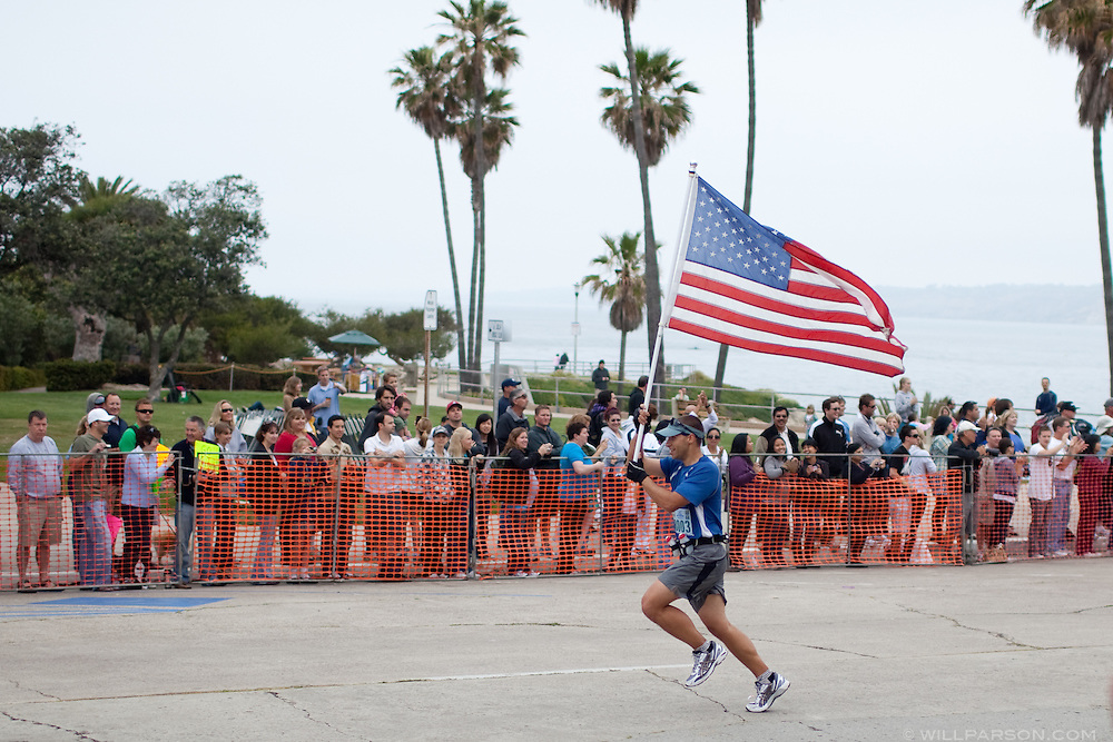 Jason Seltenright waves an American flag near the finish line of the La Jolla Half Marathon, April 25, 2010. Seltenright also carried the flag during the Carlsbad Half Marathon the previous day.