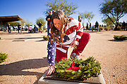 09 DECEMBER 2011 - PHOENIX, AZ:  ELIZABETH GLUCK lays a Christmas wreath on a veteran's grave in Phoenix Saturday. Several hundred volunteers and veterans gathered at the National Memorial Cemetery of Arizona in Phoenix Saturday to lay Christmas wreaths on headstones, a tradition started by Wreaths Across America. Wreaths Across America is a nonprofit organization founded to continue and expand the annual wreath laying ceremony at Arlington National Cemetery begun by Maine businessman, Morrill Worcester, in 1992.   PHOTO BY JACK KURTZ