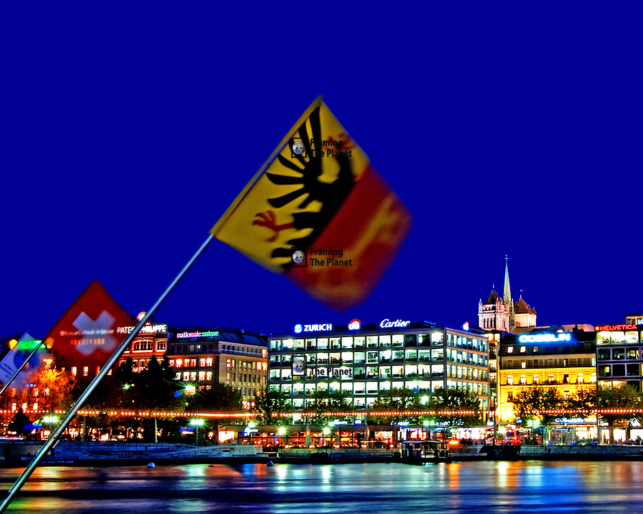 Geneva City Centre with the Swiss and Geneva Flags. This low light photograph shows an evening image of Geneva City centre with the flags of the province of Geneva and the Swiss national flag flown from the main bridge across the river that enters Lake Geneva here in the centre of the city. <br /> <br /> This image is ready to download for personal or commercial use and to order as a limited edition print. I will only make available 50 prints of this image, you can choose to have it printed on canvas or as a framed or unframed print ensuring you have an exclusive peace of highly collectable photo art to add to any home or business.