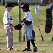A young baseball pitcher and infielder confer during the Norwalk Little League baseball competition at Broad River Fields,  Norwalk, Connecticut. USA. Photo Tim Clayton