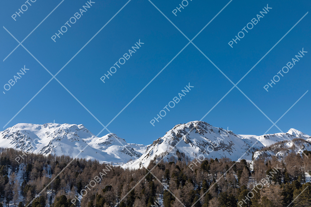 Detail of the snowy mountain top on Lukmanier on the Swiss Alps in Ticino. Blue sky