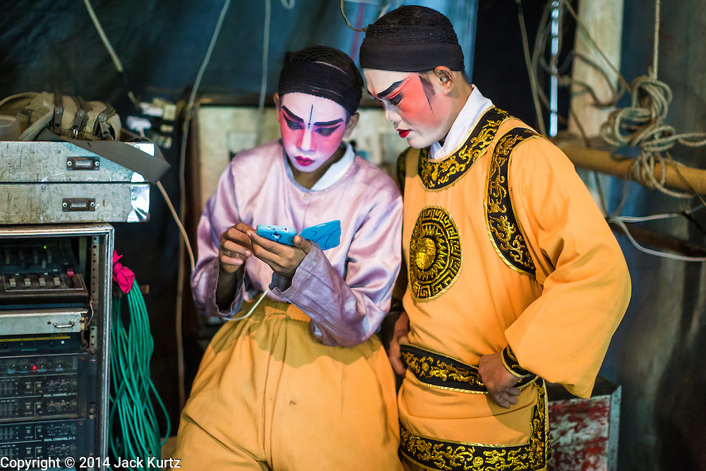 "25 JANUARY 2014 - BANG LUANG, NAKHON PATHOM, THAILAND: Performers with the Sing Tong Teochew opera troupe relax backstage during a show in a Chinese shrine in the town of Bang Luang, Nakhon Pathom, Thailand. The Sing Tong Teochew opera troupe has been together for 60 years and travels through central Thailand and Bangkok performing for mostly ethnic Chinese audiences. Chinese opera was once very popular in Thailand, where it is called ""Ngiew."" It is usually performed in the Teochew language. Millions of Chinese emigrated to Thailand (then Siam) in the 18th and 19th centuries and brought their cultural practices with them. Recently the popularity of ngiew has faded as people turn to performances of opera on DVD or movies. There are still as many 30 Chinese opera troupes left in Bangkok and its environs. They are especially busy during Chinese New Year when travel from Chinese temple to Chinese temple performing on stages they put up in streets near the temple, sometimes sleeping on hammocks they sling under their stage.     PHOTO BY JACK KURTZ"
