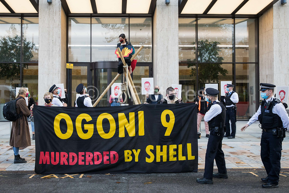 Metropolitan Police officers speak to environmental activists from Extinction Rebellion protesting outside the Shell Centre on the 25th anniversary of the killings of the Ogoni Nine on 10 November 2020 in London, United Kingdom. The Ogoni Nine, leaders of the Movement for the Survival of the Ogoni People (MOSOP) including activist Ken Saro-Wiwa, were executed by the Nigerian government in 1995 after having led a series of peaceful marches involving an estimated 300,000 Ogoni people against the environmental degradation of the land and waters of Ogoniland by Shell and to demand both a share of oil revenue and greater political autonomy.