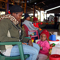 Africa, Namibia, Windhoek. A Namibian mother and her child in the open-air market of Katatura.