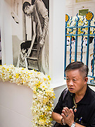 12 DECEMBER 2013 - BANGKOK, THAILAND:  A man prays next to a portrait of Somdet Phra Nyanasamvara during a mourning service for the revered Supreme Patriarch at Wat Bowon Niwet in Bangkok. Somdet Phra Nyanasamvara, who headed Thailand's order of Buddhist monks for more than two decades and was known as the Supreme Patriarch, died Oct. 24 at a hospital in Bangkok. He was 100. He was ordained as a Buddhist monk in 1933 and rose through the monastic ranks to become the Supreme Patriarch in 1989. He was the spiritual advisor to Bhumibol Adulyadej, the King of Thailand when the King served as monk in 1956. There is a 100 day mourning period for the Patriarch, the service Thursday, on the 50th day, included members of the Thai Royal Family. Although the Patriarch was a Theravada Buddhist, he was the Supreme Patriarch of all Buddhists in Thailand, including the Mahayana sect, which is based in Chinese Buddhism.    PHOTO BY JACK KURTZ