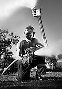 Pompier torse nue tenant une lance à incendie pour le calendrier des Anges Gardiens de Nouméa.
