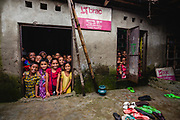"""Children looking out of a door and a window from inside a school classroom in a """"slum"""" district"""
