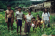 1989: Penan natives. Baru (LHS), Banai Tebai (2nd LHS) and Rasa (RHS) and extended family. Living a semi-nomadic lifestyle.Their 'sulap' temporary settlement, made from wood, bamboo and rattan is behind. Long Tedang, Sarawak, Borneo.<br /> <br /> Tropical rainforest and one of the world's richest, oldest eco-systems, flora and fauna, under threat from development, logging and deforestation. Home to indigenous Dayak native tribal peoples, farming by slash and burn cultivation, fishing and hunting wild boar. Home to the Penan, traditional nomadic hunter-gatherers, of whom only one thousand survive, eating roots, and hunting wild animals with blowpipes. Animists, Christians, they still practice traditional medicine from herbs and plants. Native people have mounted protests and blockades against logging concessions, many have been arrested and imprisoned.