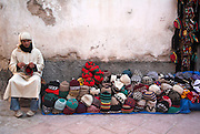 Man selling wool hats from a street stall Essaouira, Morocco, north Africa