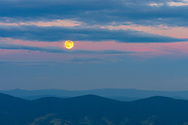 Deep blue hues born of the fading sun settle over the mountains above Virginia and West Virginia from high atop Spruce Knob, broken only by stripes of pink sky through the slits of shifting clouds revealing the mid-summer moon to usher in the night.