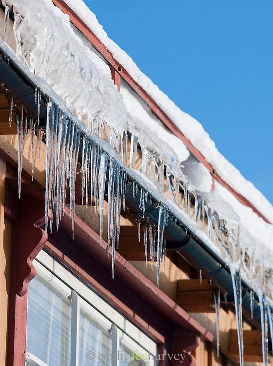 Icicles hang from the frozen guttering of a rooftop in Tromso, Norway