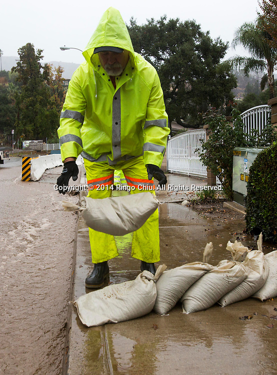 A man places sandbags as mud and debris flow down along a street from the burnt areas in Glendora, California, Tuesday, December 2, 2014. The rain, along with gusty winds, is the result of a Pacific storm system. Forecasters said the storm should drop about 1 to 2 inches of rain along the coast and in valley areas, and 2 to 5 inches in the mountains and foothills.(Photo by Ringo Chiu/PHOTOFORMULA.com)