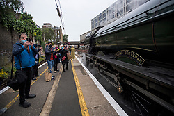© Licensed to London News Pictures. 20/05/2021. London, UK. Train enthusiasts and passengers take photographs of The LNER Flying Scotsman steam locomotive at Victoria Station in central London ahead of a tour through the Surrey Hills in South east England. The heritage steam locomotive touring season was mostly cancelled last year due to the Covid-19 pandemic but is now underway as restrictions are eased. Built in 1923 for the London and North Eastern Railway (LNER)It was the first steam locomotive to reach 100 miles per hour . Photo credit: Ben Cawthra/LNP