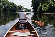 The rear view of a woman canoeist who his paddling on the River Yare near Thorpe St Andrew, on 2nd July 2021, in Norwich, Norfolk, England.