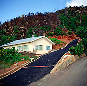 Population pressure leading to deforestation and building development on steep mountain slopes, Mahe, Seychelles
