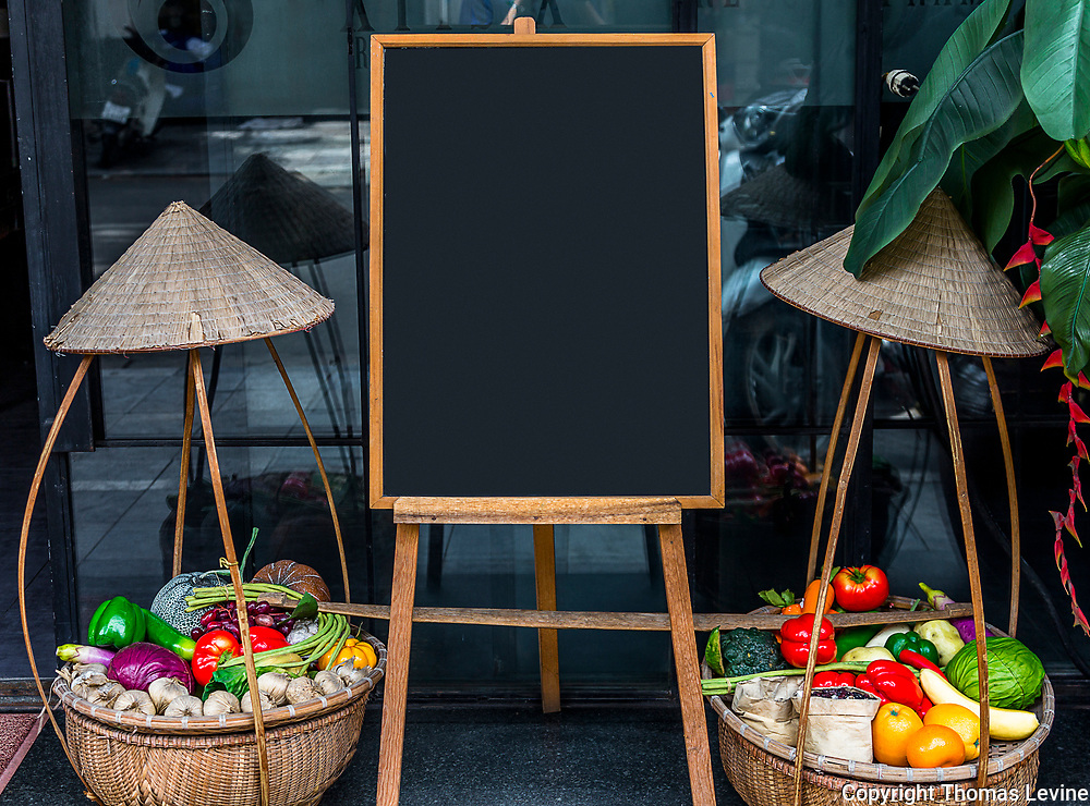 Front of a restaurant with a blank restaurant sign between two baskets of fruit. Copy Space. Use for Advertising, menu, or a message on social media.