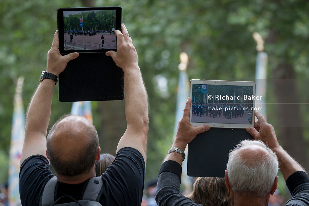 On the 100th anniversary of the Royal Air Force (RAF) and before an historic flypast of 100 aircraft formations representing Britain's air defence history which flew over central London, the public watch a march past of service personnel, on 10th July 2018, in London, England.