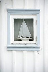 Detail of sailing boat in window of wooden house in village of Fiskebackskil  on Bohuslan coast in Vastra Gotaland Sweden
