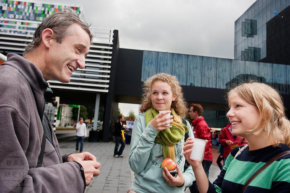 Pater Alain-Dominique (links) van de Utrechtse geloofsgemeenschap Familie van Sint Jan praat met eerstejaars studentes tijdens de informatiemarkt van de introductieweek.<br /> <br /> Father Alain-Domique (left) of the brothership Sint Jan is talking to students during their introduction week.