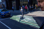In an area of reflected striped light, a man crosses Threadneedle Street in front of stopped traffic in the City of London - the capital's financial centre (aka The Square Mile), on 27th September 2018, in London, England.