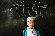 Young student with blackboard at Muslim School and Mosque in Mawlamyine, Myanmar