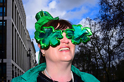 © Licensed to London News Pictures. 17/03/2019. LONDON, UK.  A woman watches the annual St. Patrick's Day parade and festival in the capital.  Photo credit: Stephen Chung/LNP
