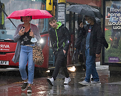 © Licensed to London News Pictures. 07/08/2021. London, UK. Members of the public get caught in a downpour of rain in Wood Green, North London. Heavy rain is expected to cause flash flooding in parts of the UK. Photo credit: Ben Cawthra/LNP