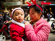 24 DECEMBER 2017 - HANOI, VIETNAM: A woman and her son in Christmas attire on a street in the old quarter of Hanoi. The commercial and gift giving aspect of Christmas is widely celebrated in Vietnam and Vietnam's 5+ million Catholics celebrate the religious aspects of Christmas.     PHOTO BY JACK KURTZ