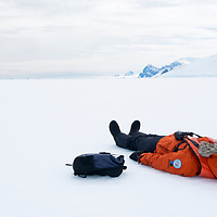 A guest lies on their back on the fast ice to enjoy the special moment while in Crystal Sound in Antarctica.