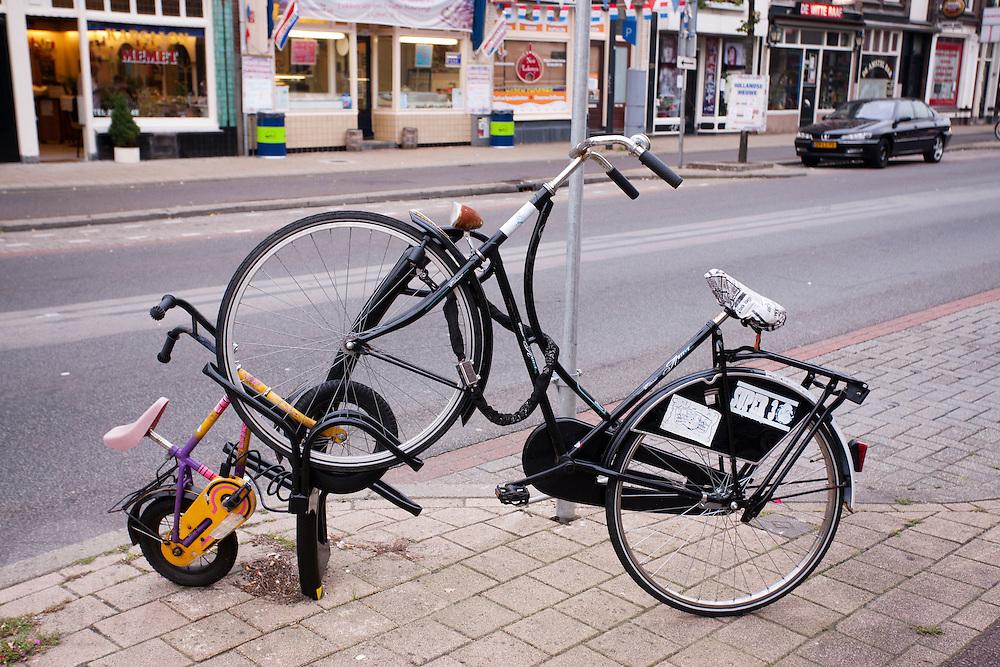 Een oma- en een kinderfiets staan keurig in het fietsenrek aan de Amsterdamsestraatweg in Utrecht.<br /> <br /> Two bikes are parked at the Amsterdamsestraatweg in Utrecht.