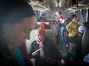 A mix of uighur people (a woman doing embroidery on the foreground) return back to Kashgar after spending time in Hotan for work or family visit. Train is the cheapest means of transportation in this part of China. It cost about 20 Yuan to travel from Hotan to Kashgar (about 4 times cheaper than bus). Life inside the train - mostly Muslim Uighur people  ride this train.