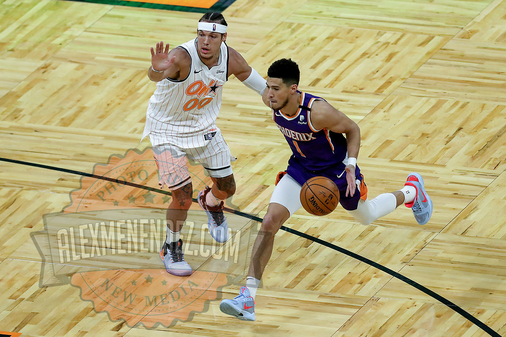 ORLANDO, FL - MARCH 24: Devin Booker #1 of the Phoenix Suns drives to the net past Aaron Gordon #00 of the Orlando Magic during the first half at Amway Center on March 24, 2021 in Orlando, Florida. NOTE TO USER: User expressly acknowledges and agrees that, by downloading and or using this photograph, User is consenting to the terms and conditions of the Getty Images License Agreement. (Photo by Alex Menendez/Getty Images)*** Local Caption ***Devin Booker; Aaron Gordon