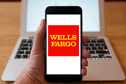 Using iPhone smartphone to display logo of Wells Fargo , the American international banking and financial services holding company