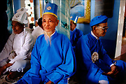 Elders of the Cao Đài faith, a syncretistic, monotheistic religion established in the Vietnamese city of Tây Ninh, meditate inside their grand temple.  <br />© Steve Raymer