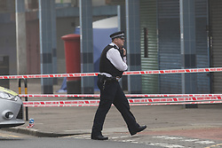 April 3, 2017 - London, London, UK - LONDON, UK.  A police officer walks past the forensic tent at the crime scene and police cordon around BJ Wines and parade of shops in Freemasons Road, Canning Town, east London. Ahmed Jah, 21 is reported to have been knifed inside the off license, BJ Wines in Freemasons Road yesterday afternoon after he was set upon by a gang of men and stabbed in the chest. Emergency ambulance services attended and the man was pronounced dead at the scene shortly after. (Credit Image: © Vickie Flores/London News Pictures via ZUMA Wire)