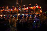 Costumed men on a float belonging to the Krewe of Endymion travel down Canal Street and throw beads and other knickknacks to the crowd during Mardi Gras. In the foreground a woman raises her arms, preparing to catch the plastic item just tossed from the float.