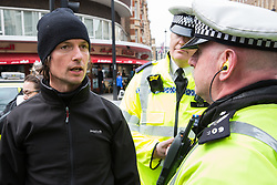 London, UK. 16th April 2019. A police officer asks a man who had been praying at a religious service in Edgware Road to identify himself during the second day of International Rebellion UK activities by climate campaigners from Extinction Rebellion to call on the Government to take urgent action to address climate change.