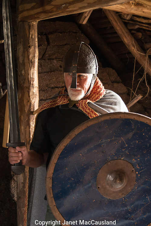 Ed is dressed in historic Nordic costume with helmet, sword, and shield, while inside a sod house in L'ans Aux Meadows, Newfoundland, Canada.