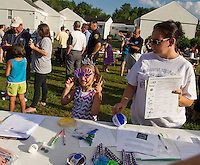 Izabella Peavey tries on a pair of purple helping hand glasses with Lisa Brousseau while stopping by the Laconia Police table set up at Laconia's National Night Out Tuesday evening.  (Karen Bobotas/for the Laconia Daily Sun)